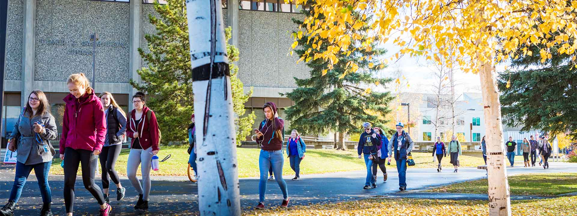 Students walking past the Rasmuson Library on a fall afternoon