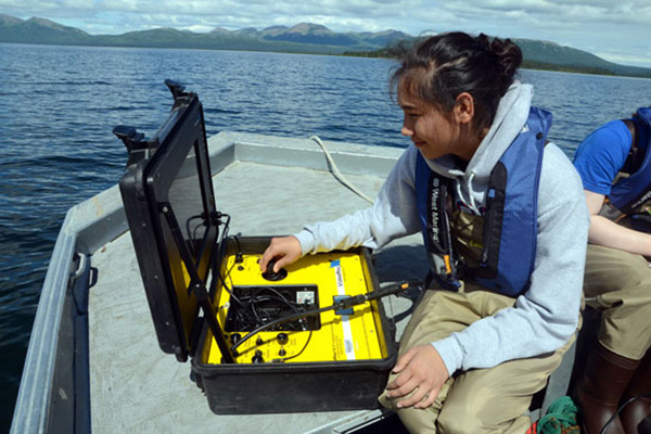 Student using testing equipment on a boat