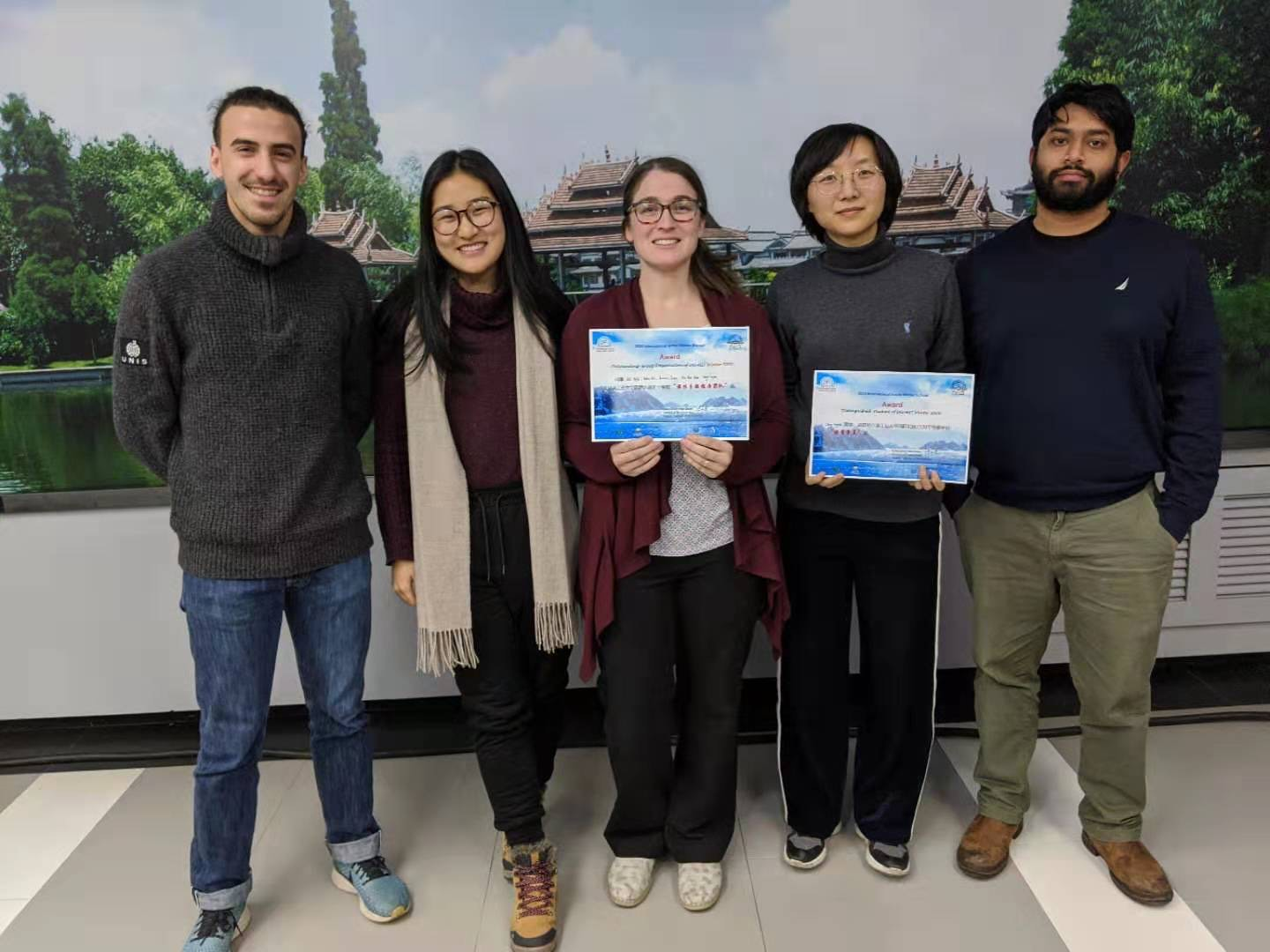 Five students stand holder award certificates
