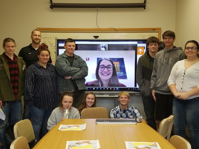 A group of people stand around a video screen with a picture of a woman videoconferencing in on it.