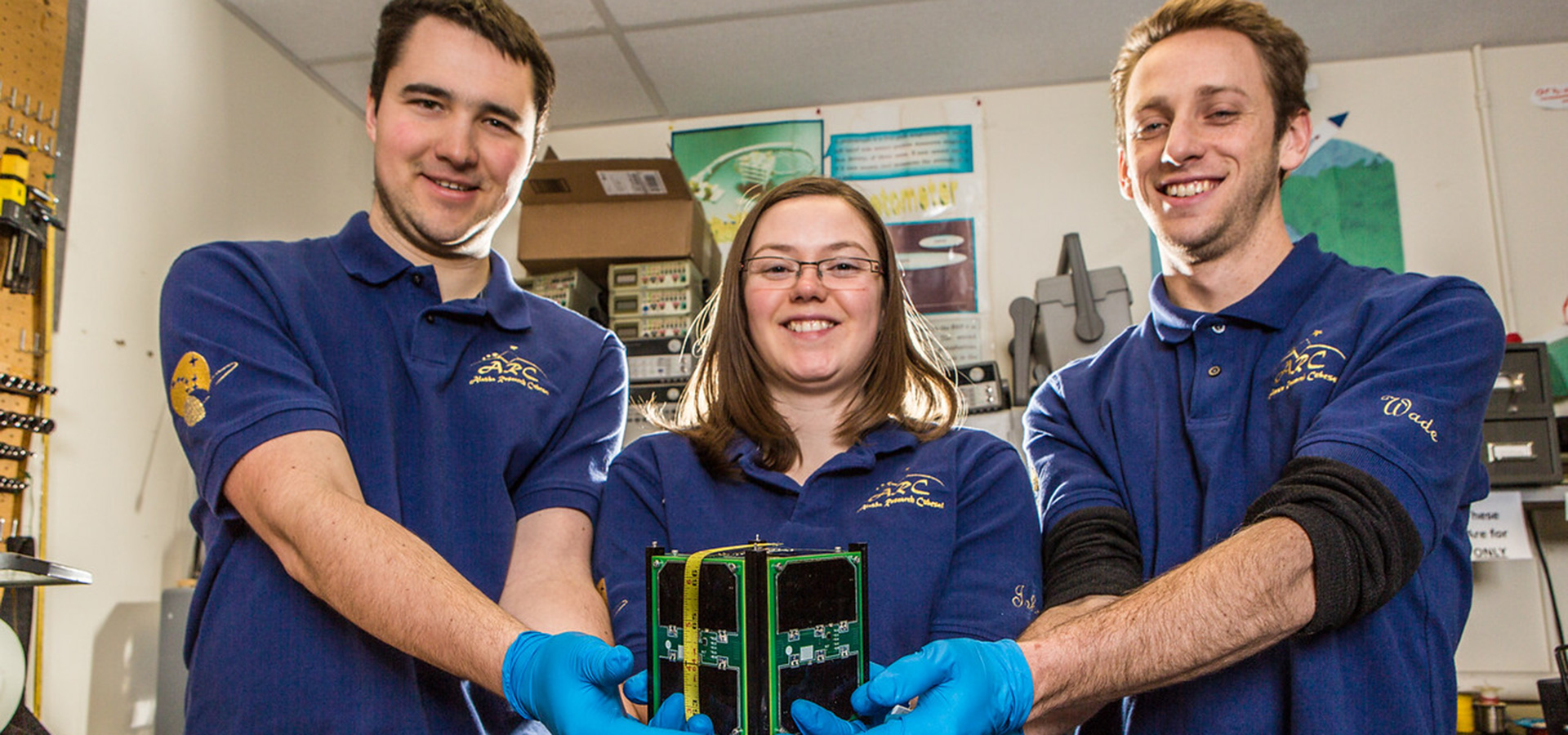 Students holding CubeSat