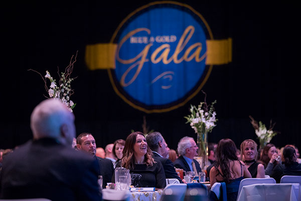 Smiling attendees seated at tables at the UAF Blue and Gold Celebration