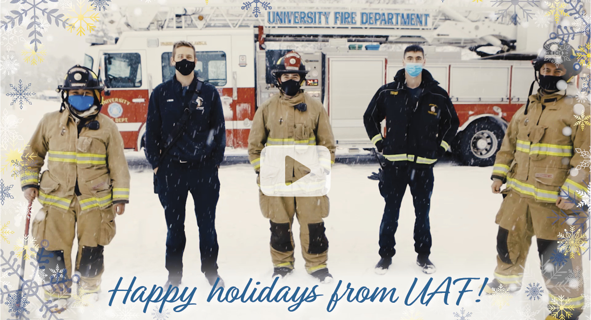 Graphic with photo of UAF firefighters wearing masks in the background, blue and gold snowflakes and blue text that reads Happy holidays from UAF in the foreground