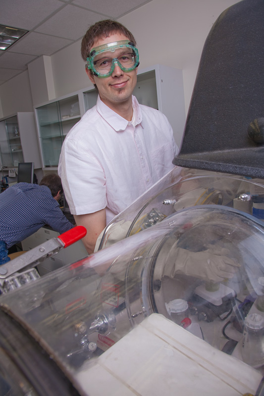 Dr. Chris Iceman works in a glove box in Dr. Tom Trainor's Environmental Chemistry research laboratory.