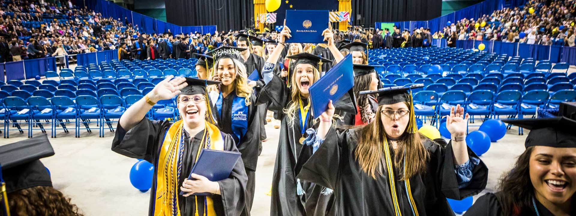 Celebrating students proceed out of the Carlson Center after the 2018 commencement ceremony