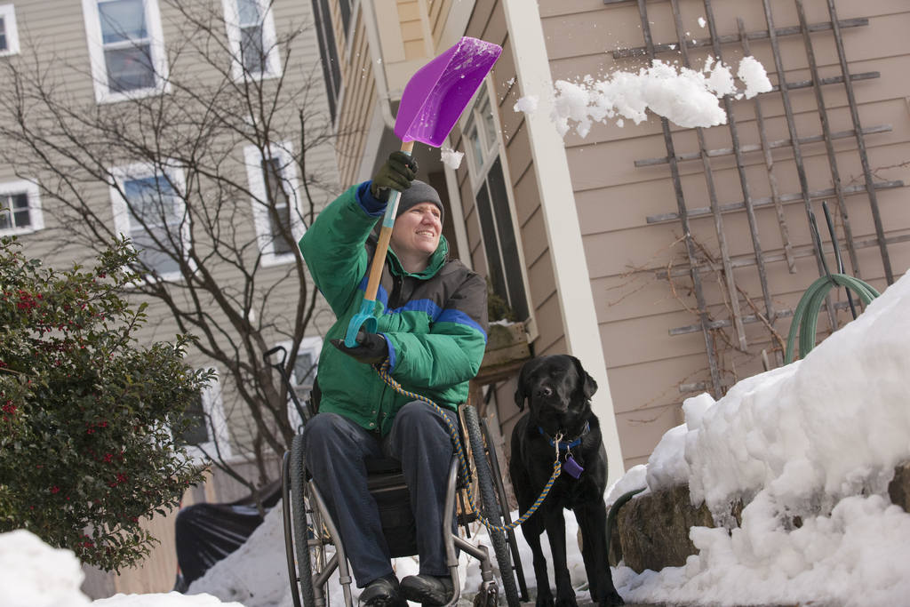 a person in a wheelchair shovels snow while accompanied by a service dog