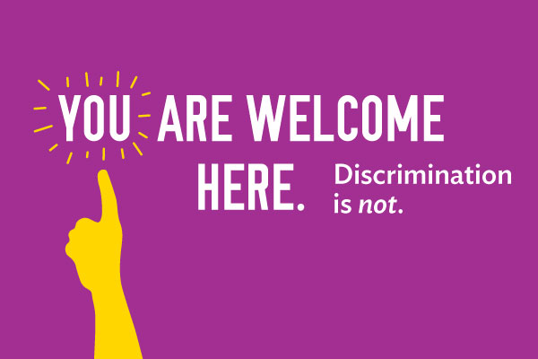 Purple poster that says, You are welcome here. Discrimination is not.