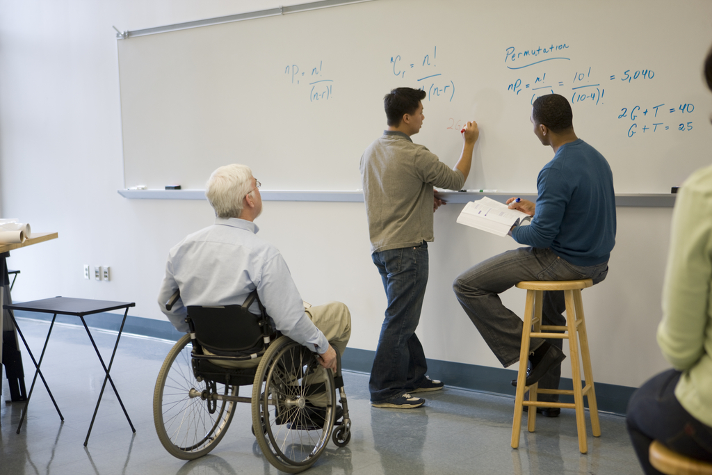 a professor in a wheelchair looks on as two students work out an equation on a whiteboard