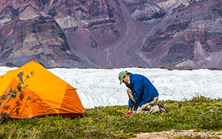 Researcher camping on snow covered mountain