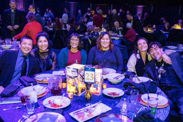 Attendees of the 2019 Blue and Gold Celebration smile around their table