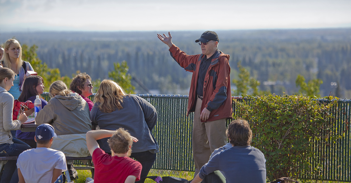 UAF history professor Terrence Cole, in black hat, lectures his History of Alaska students outdoors on the first day of classes of the fall semester.