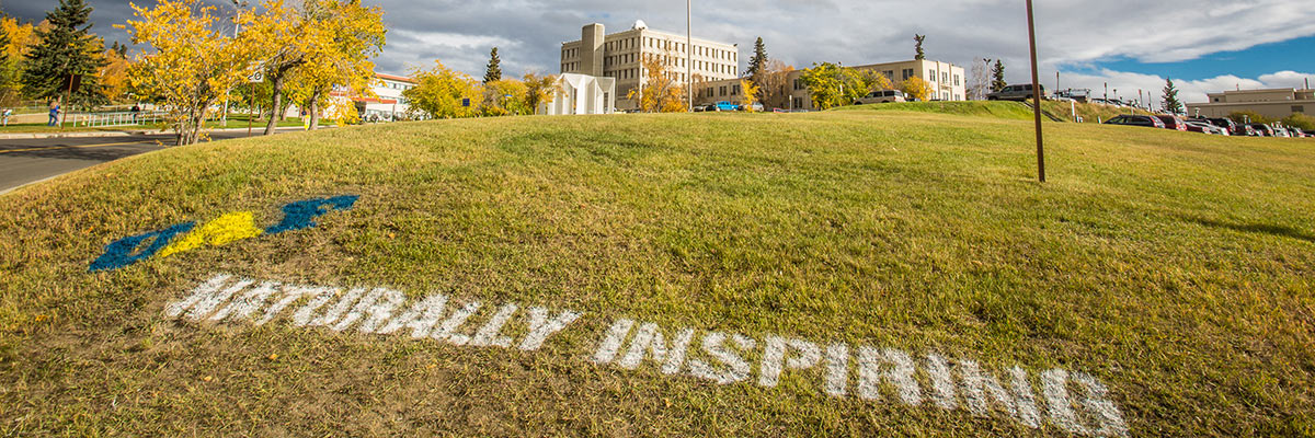 Naturally Inspiring tag on the lawn at UAF