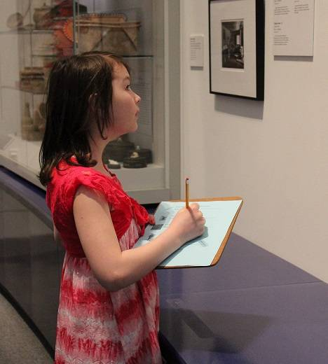 Child holding a clipboard and activity sheet, and looking at a museum exhibit.
