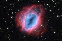 A blue and pink nebula in a starry sky.