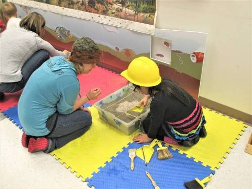 Adults and children dig for fossils in a sandbox.