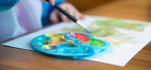 A child's hands holding a paintbrush next to a plate with several colors of paint.