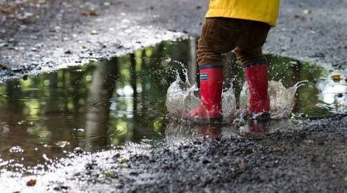 Child wearing red rubber boots splashing in a mud puddle.