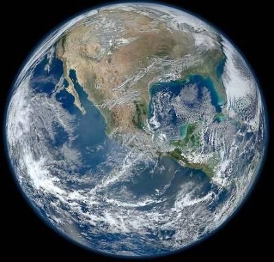 The Earth as seen from outer space, with oceans, part of North America, and clouds visible.