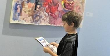 A child looks at a colorful abstract painting by Alfred Skondovitch.