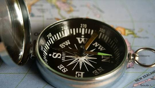 Close-up of a compass sitting on top of a world map.