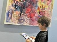 Child looking at a colorful abstract painting by Alfred Skondovitch.