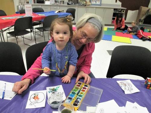 An adult and child sit at a table painting with watercolors.