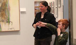 A docent talking to a child. The child is pointing at a painting.