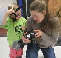 Student kneeling next to a child and showing a camera to the child.