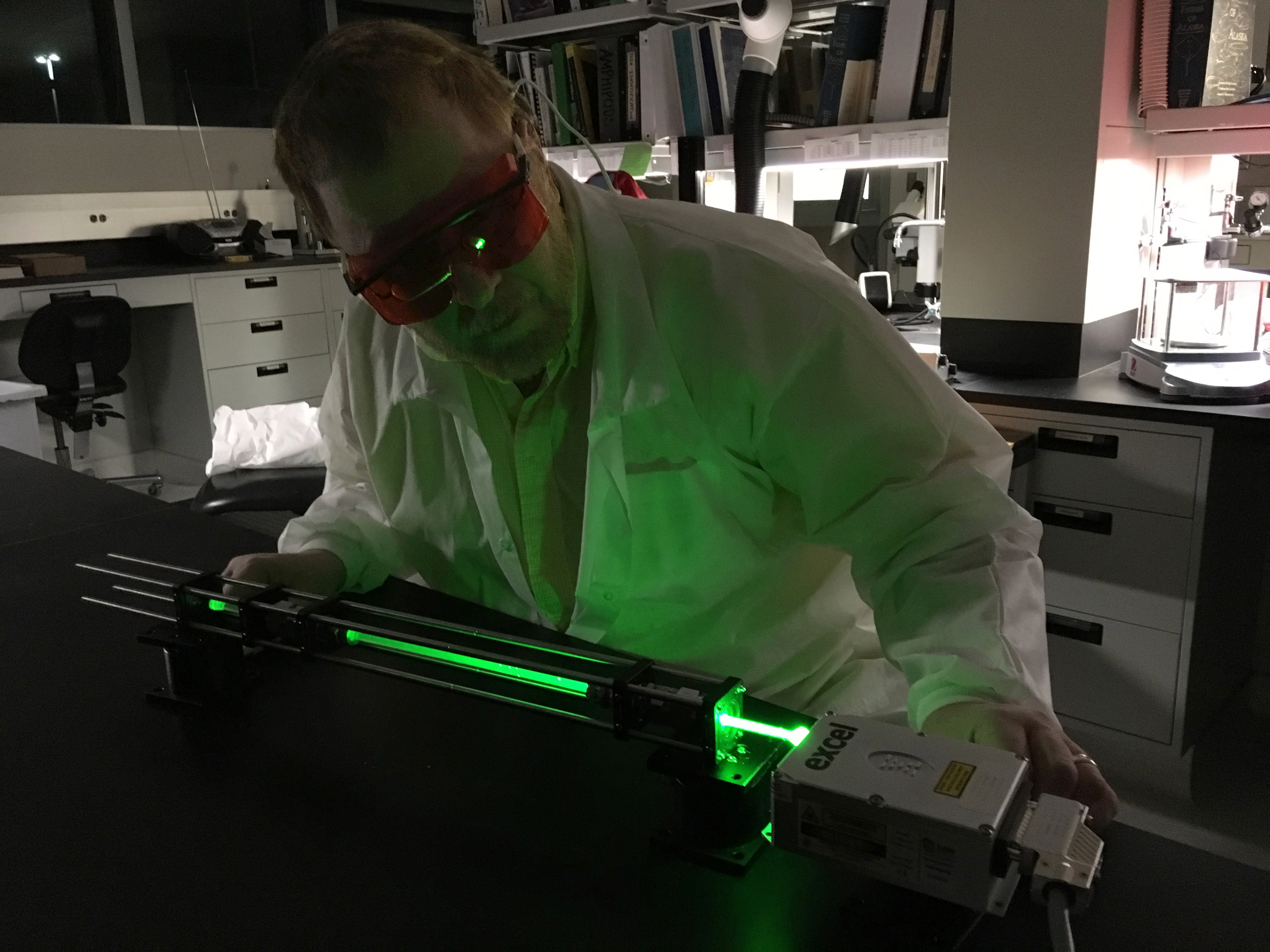 Wearing eye protection against an intensely green laser, Jonathan Kamler examines a new, not-yet-silvered, capillary.