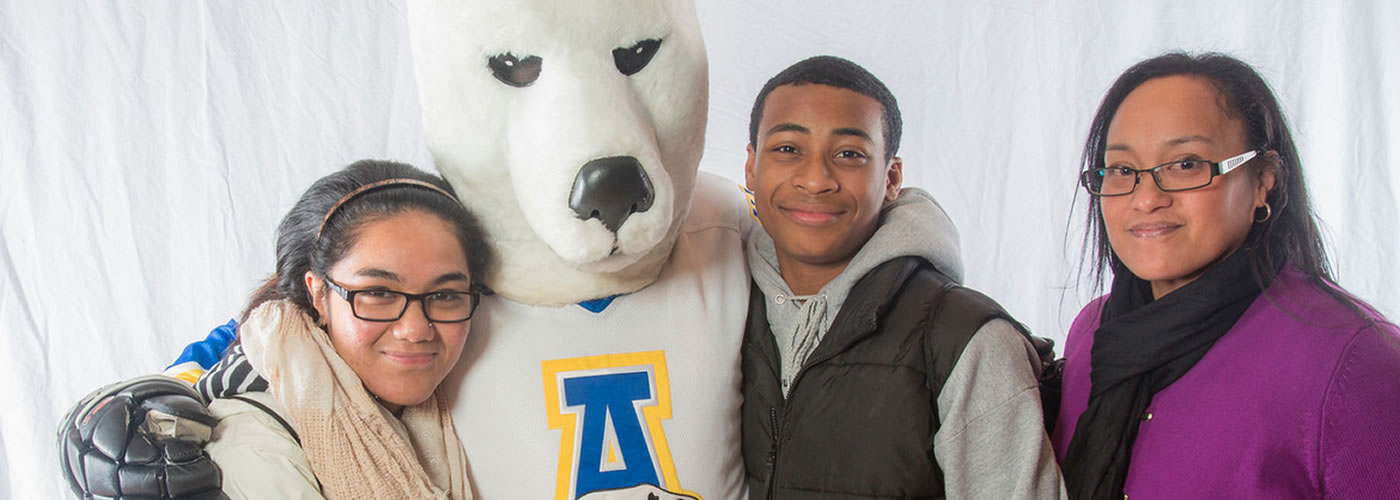 Prospective students and their parent pose with the UAF Nanook mascot at campus preview day.