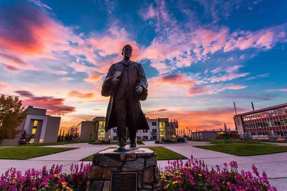 The Bunnell statue stands in Cornerstone Plaza on the Fairbanks Campus with the summer sunset in the background