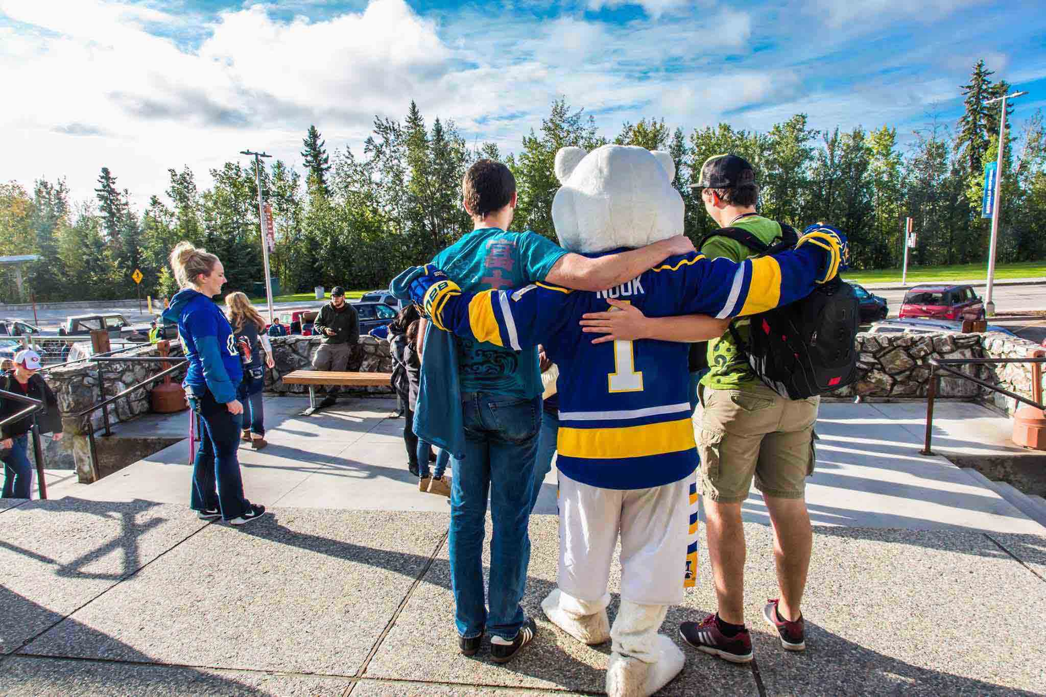 Two MBS residents embrace the Nanook mascot on move-in day