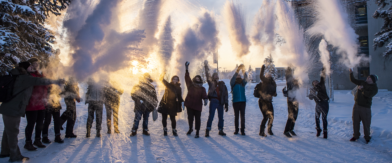 UAF students toss water into the air that instantly freezes on a frigid winter day