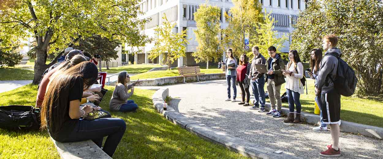 A group of students enjoy outdoor class outdoors at the UAF Constitution Plaza