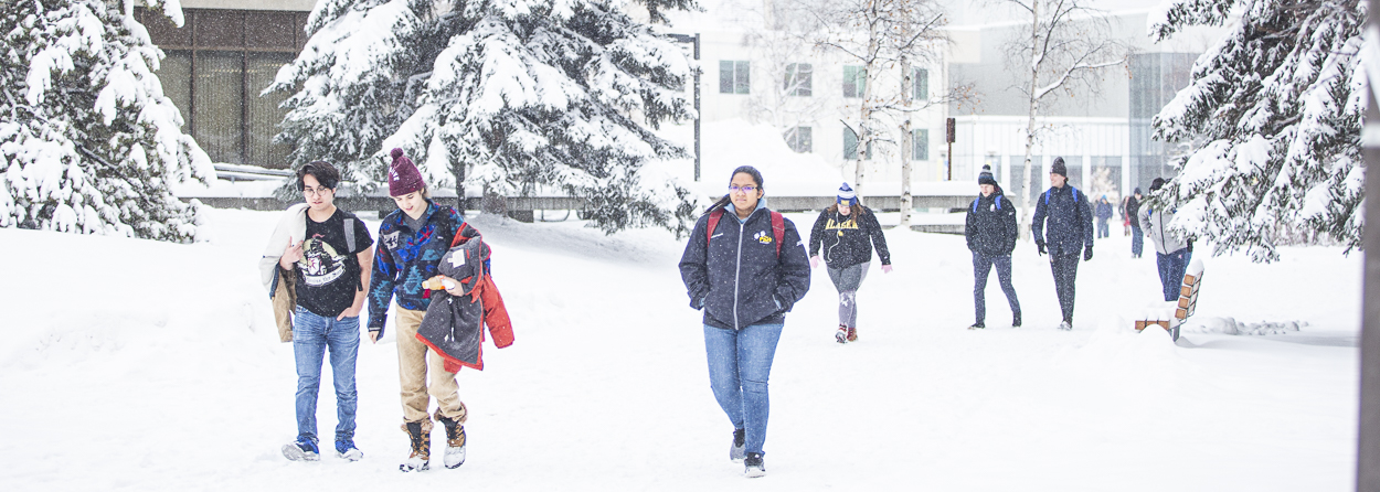 UAF students walking across the Fairbanks campus on a bright snowy day.