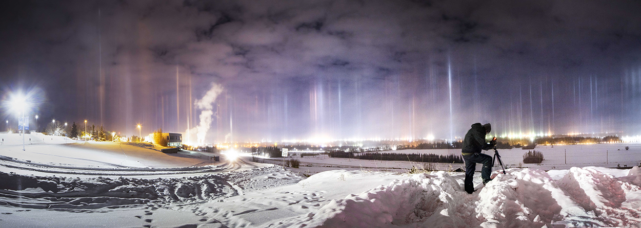 Light beams shine up through the ice fog at night on the UAF campus