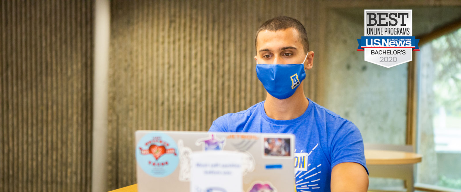 A student wearing a mask sits at a table with a laptop in the Wood Center multilevel lounge.