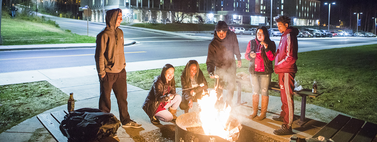 UAF students roast marshmallows around a fire pit on campus