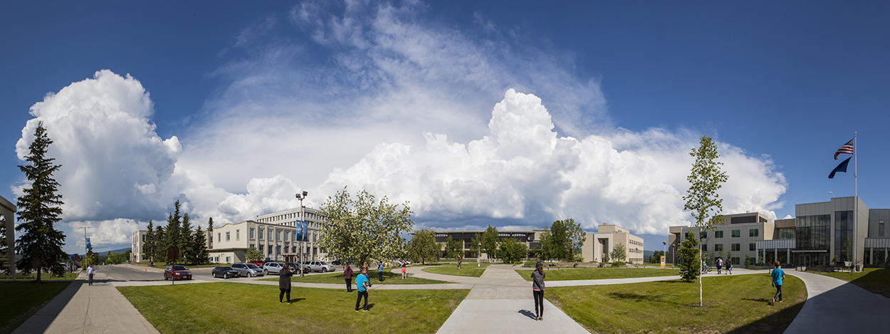 Panoramic view of students walking through Cornerstone Plaza on the Fairbanks campus in summer
