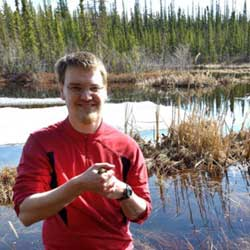 UAF doctoral degree student Don Larson standing near Ballaine Lake and holding a wood frog