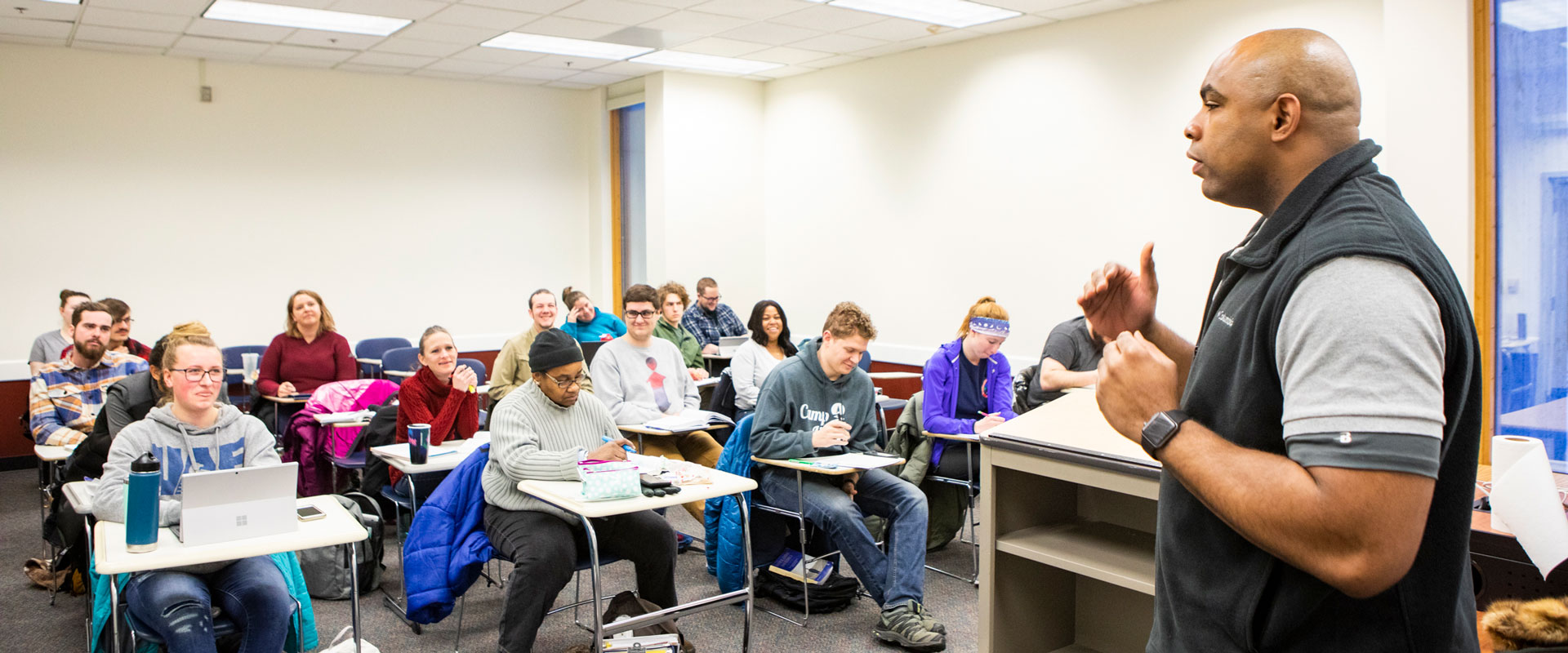 A faculty member lecturing a classroom full of students