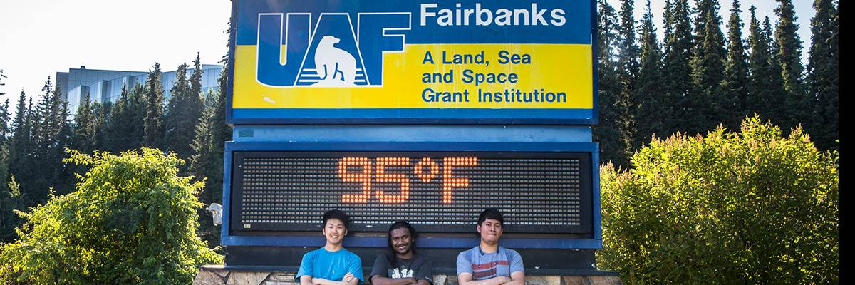Three UAF students pose in front of the campus time and temperature sign, which reads 95 degrees, Fahrenheit