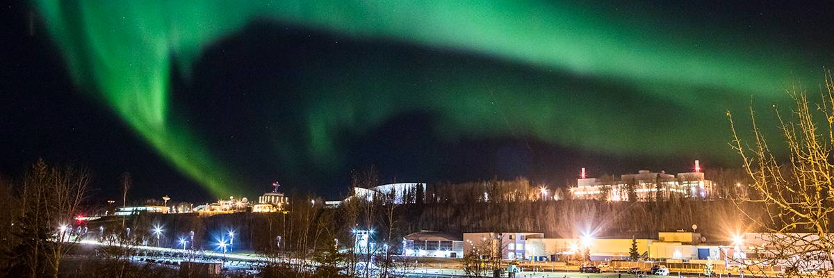The Aurora Borealis is seen over the UAF campus on a dark winter night