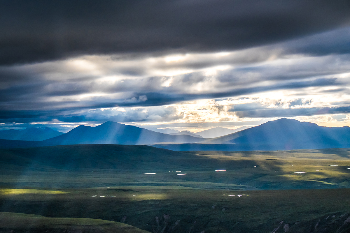 Sunlight filters through the clouds on a July evening in Alaska's eastern Interior.